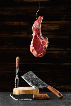 Photo pour Beef ribeye steak bone-in on steel hook over the forged butcher set - image libre de droit
