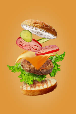 Photo pour Burger with flying ingredients isolated on orange background - image libre de droit