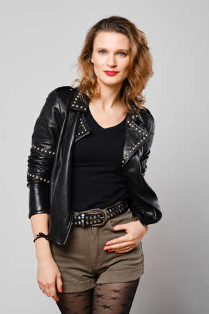 Photo pour Studio portrait of trendy woman in leather jacket and shorts with natural make up and red lips - image libre de droit