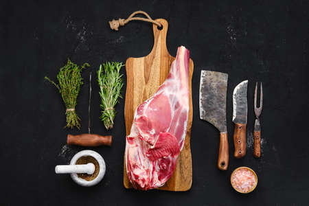Photo pour Fresh raw lamb leg bone in on wooden cutting board with herbs and seasoning - image libre de droit
