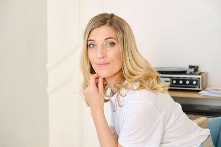 Foto de Lovely woman in white t-shirt and blue skirt sits on chair in livingroom - Imagen libre de derechos