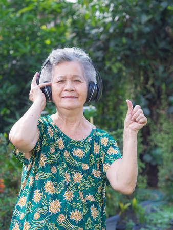 Photo pour Senior woman standing wearing wireless headphone listening to a favorite song, and smile happy in garden. Asian old woman, short white hair are enjoying the music. Makes her have good mental health - image libre de droit