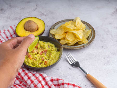 Photo pour Fresh guacamole bowl with potato chips on a plate placed on a gray stone background. Healthy and easy to make at home with a few simple ingredients. Excellent as party food or at bars. - image libre de droit