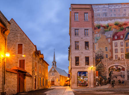 Photo for Quebec, Canada - October 16, 2018: Early Morning View of Notre-Dame-des-Victoires Church and murals of Quebec city in Place Royale of Old Quebec city, Canada. - Royalty Free Image