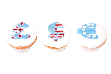 pound, dollar and euro signs on cup cakes on white .