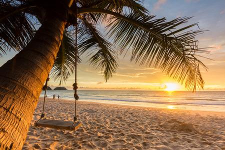 Foto de Woodden swing under coconut tree on the beach with sunset background - Imagen libre de derechos