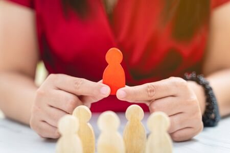 Figure in human resource management concept. The red wood figure was picked out of its group. Red Wood figure like who is selected from the candidate, or choose the most dominant in the team