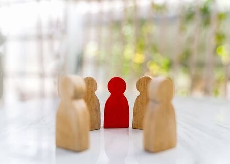 Figure in human resource management concept. The group of wooden puppets is a circular. A red wooden figure like an dominant in a group with blur bokeh background