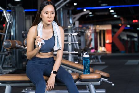 Photo for Asian women are sitting on the exercise and are holding towels with water bottles placed on their sides. She's sitting alone at the gym in sport healthy concept - Royalty Free Image