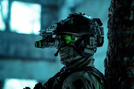 Photo pour Closeup man uniform with machine gun and turned on night vision device. Airsoft soldier with green light on face in night building. Side view. - image libre de droit