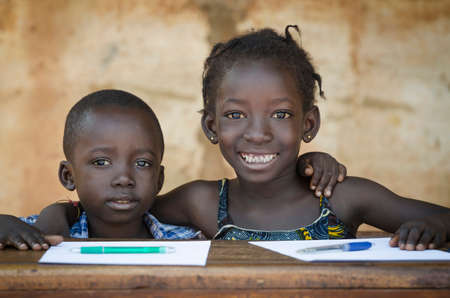 Photo pour Education Symbol: Couple of African Children Smiling at School. Back To School Symbol - African Girl Toothy Huge Smile Showing Red Pencil - image libre de droit