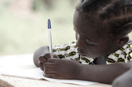 Photo pour Cute African schoolgirl doing her homework at school: beautiful black girl writing and learning activity with a blue pen. She's sitting in her desk doing her calculating work in her exercise book. - image libre de droit