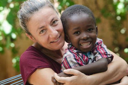 Photo pour Adoption symbol - Woman adopts a little African boy - image libre de droit