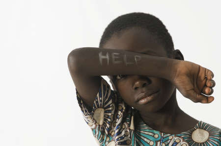 Little African boy asks for help by covering his face with his arm, isolated on white