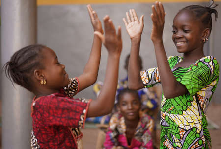 Photo pour Two Little African Girls Performing A Hand Clapping Game - image libre de droit