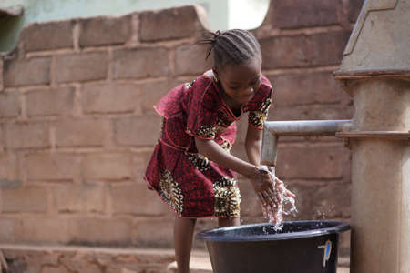 Photo for Small African Girl Washing Her Hands At The Village Well - Royalty Free Image