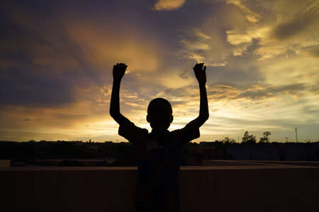Photo for Handsome African Boy Waves in front of Evening Sun - Royalty Free Image