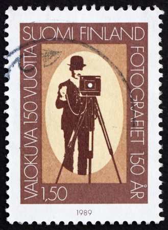 FINLAND - CIRCA 1989: a stamp printed in the Finland shows Photographer and box camera, 150th anniversary of photography, circa 1989