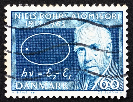 DENMARK - CIRCA 1963: a stamp printed in the Denmark shows Niels Bohr and Atom Diagram, 50th anniversary of atom theory, circa 1963