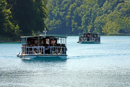 CROATIA PLITVICE, 16 JULY 2011: Beautiful lake with two river boats on the blue water between green hills
