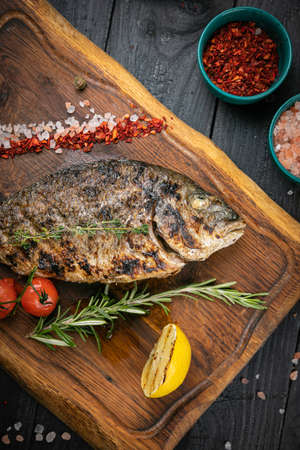 Photo pour Grilled Dorada fish, sea bream with the addition of spices and lemon on the desk, top view - image libre de droit