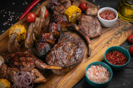 Photo pour Assorted delicious grilled meat with vegetable and herbs on rustic table - image libre de droit