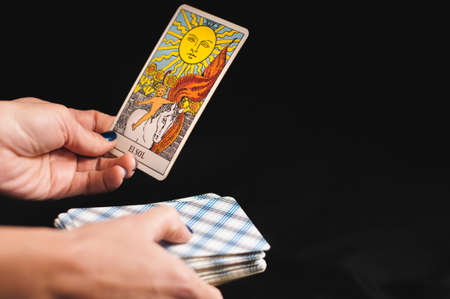 Photo for Tarot cards senior Arcana in the hands of a woman on a black background - Royalty Free Image