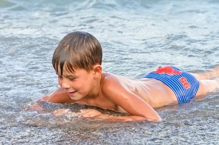 Photo pour Boy playing in the surf. summer sea - image libre de droit