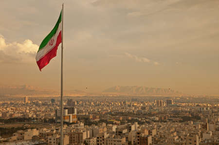 Iran flag waving  in the wind above skyline of Tehran lit by orange glow of sunset