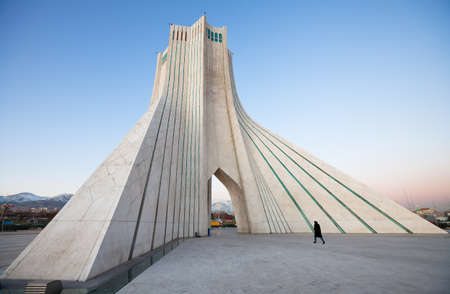 Azadi monument, the famous landmark of Tehran, with a pedestrian walking by