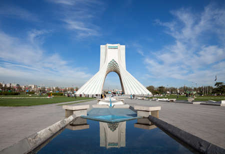 Azadi monument and its reflection on waterways in Azadi square of Tehran, against blue sky and white clouds.
