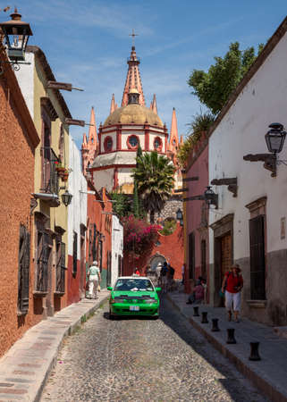 Photo for SAN MIGUEL DE ALLENDE, MEXICO - MARCH 26, 2011: Green taxi in front of Parroquia de San Miguel Arcangel. The gothic facade of this local parish church was inspired by Gaudi Sagrada Familia. - Royalty Free Image
