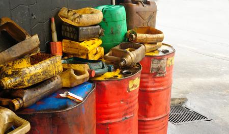 Photo pour Dirty & oily plastic canisters on waste oil barrels tank - image libre de droit