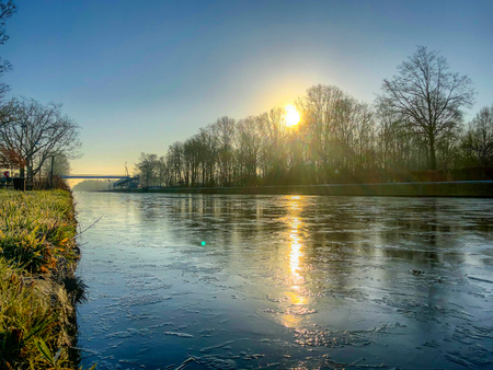 Photo pour Dramatic and colorful sunrise or sunset over a beautiful landscape with a river or canal, treelined riverside and grass at sunrise creating a tranquile and quiet scenic nature background - image libre de droit