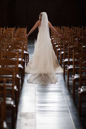 Foto per Beautiful bride in luxurious wedding dress walking between the chairs of a church with beautiful bouquet. Beautiful bride with stylish make up and hair style. Young bride posing in white dress. Black and white. High quality photo - Immagine Royalty Free