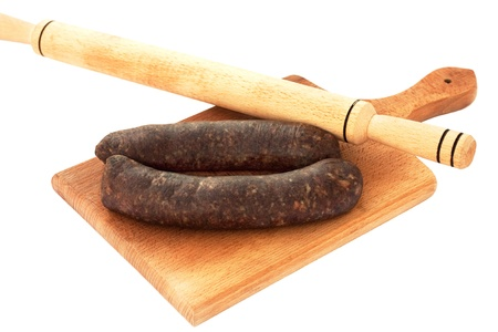 Raw,home made sausages ready to be rolled with rolling-pin on wooden chopping board isolated on white
