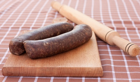 Raw,home made sausages ready to be rolled with rolling-pin on wooden chopping board