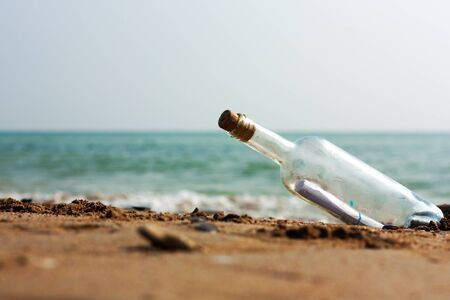 A Letter in a bottle on the shore,cast out by ocean or sea
