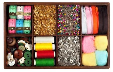 Assortment of different   tailoring materials  tape-measure,safety pins,needles,zippers,buttons,spivels,threads and cottons   in vintage or retro wooden box isolated on white background