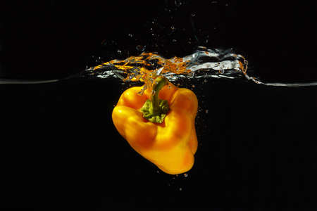 Fresh yellow pepper falling into the water with a splash on a black background