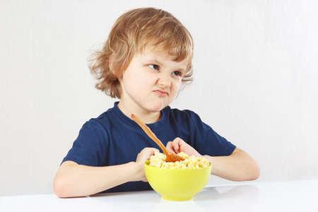 Little cute blonde boy refuses to eat a porridge