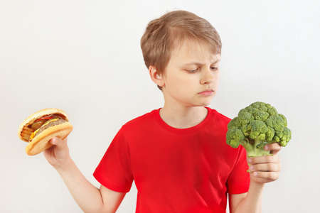 Photo pour Boy chooses between fastfood and broccoli on a white background - image libre de droit