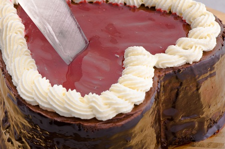 Chocolate cake in shape of a hearth is being cut