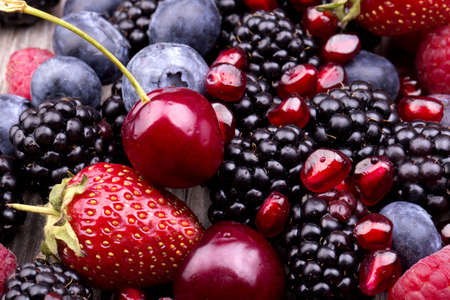 Photo for  tasty summer fruits on a wooden table. Cherry, Blue berries,  strawberry, raspberries, Blackberries, pomegranate - Royalty Free Image
