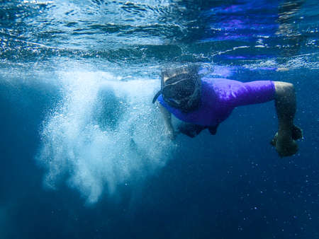 Photo pour An image of a man diving in the sea underwater with lots of air bubbles - image libre de droit