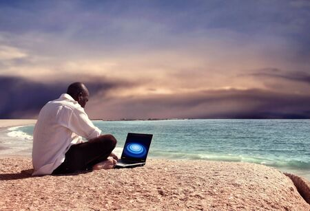 black man with laptop on the beach