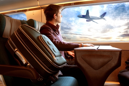 man on the train looking sunset and airplane