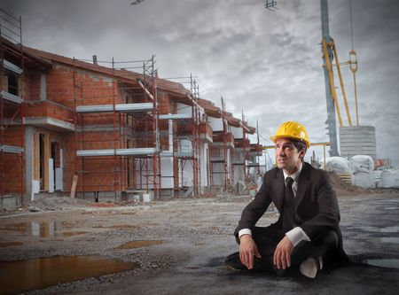 Businessman with helmet sitting in a construction site