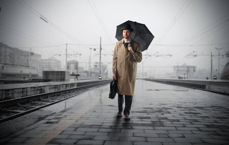 Gentleman with umbrella standing on a platform of a train station