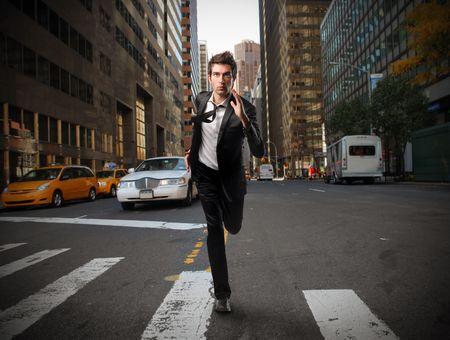 Businessman running on a city street